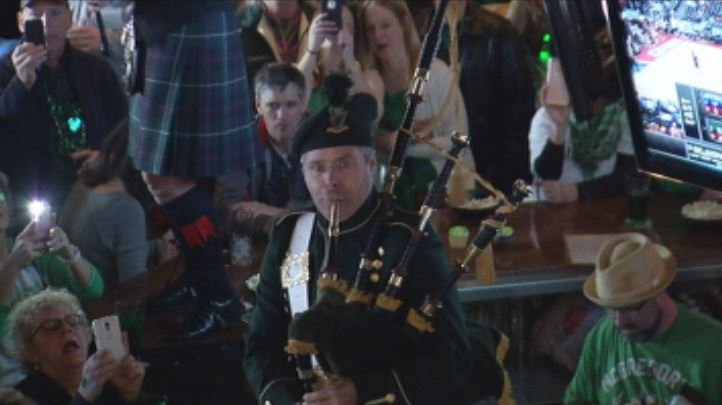 A bagpipe player standing on the bar