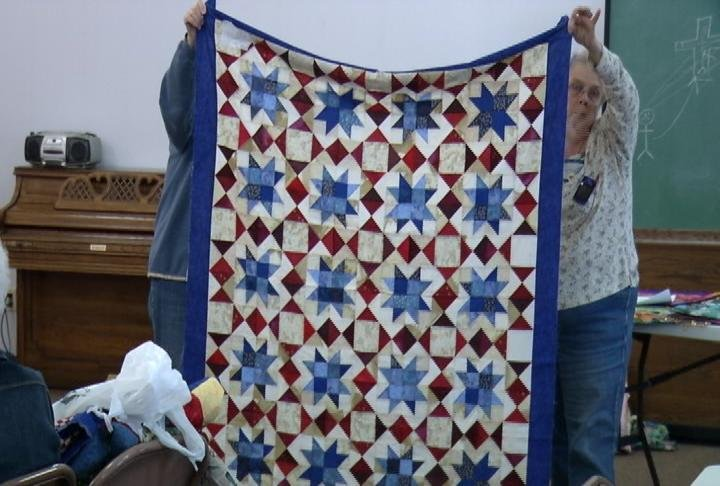 Two members of The Keepsake Quilt Guild hold up a quilt made by one, as part of the show-and-tell portion of the monthly meeting.