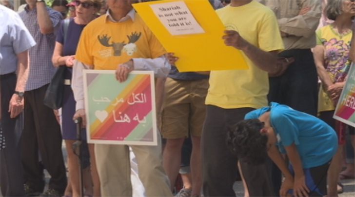 Muslim supporters deliver a message of peace to anti-Muslim protesters
