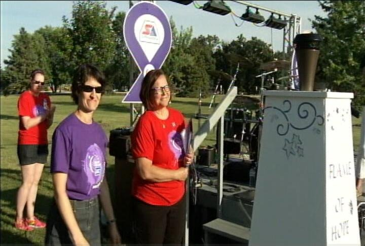 Becky Waara stands with cancer survivor at Relay for Life of Olmsted County 2016, following the lighting of the torch.