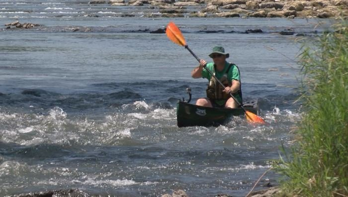 A man enjoys a hot July day kayaking on the new rock rapids in Oronoco.