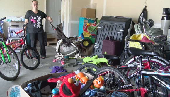 Alicia Ober shows off some of the donated items in her garage
