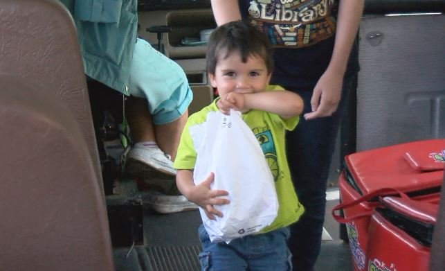 A young boy enjoys his free sack lunch onboard the Fuel Up bus.
