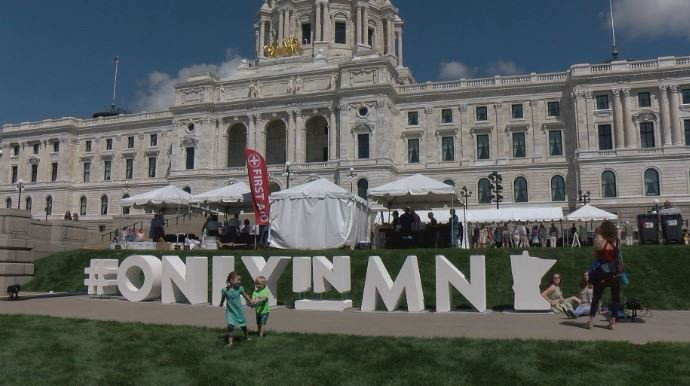 Visitors taking a look at the Only in MN hashtag on the capitol's front lawn.