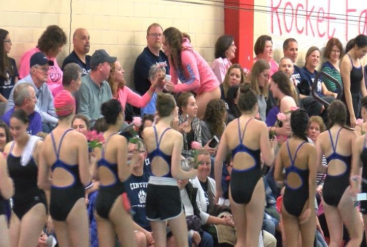 Swimmers handed out pink flowers to loved ones on the bleachers