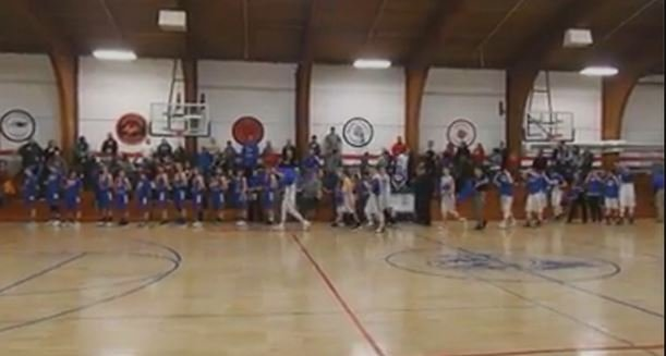 Grand Meadow basketball team members take off 'MC Strong' t-shirts to give to Mabel-Canton players