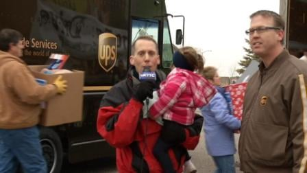 "Ted Schmidt and daughter Julia reporting ""live"" as UPS drops off boxes of toys"