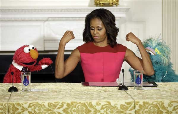First lady Michelle Obama, center, flexes her arms for PBS Sesame Street's characters in October 2013.