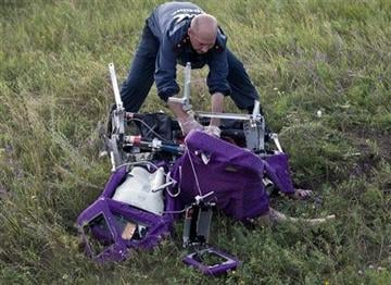 (AP Photo/Vadim Ghirda). An emergency worker cuts through aircraft seat belts to free the body of a victim at the crash site of Malaysia Airlines Flight 17 near the village of Hrabove, eastern Ukraine, Saturday, July 19, 2014.