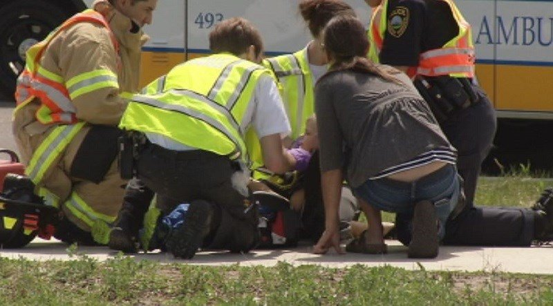 Emergency crews check the neck and head of a child injured in a crash on West Circle Drive in Rochester.